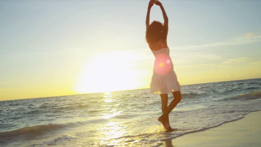 Happy Latin American girl having fun beach on luxury island at sunrise shot on RED EPIC