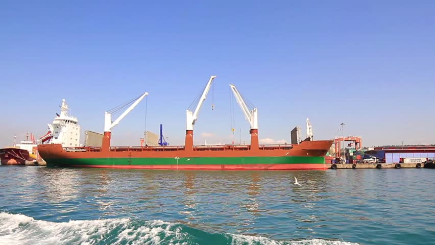 Bulk carrier cargo ship with deck cranes under loading in seaport.