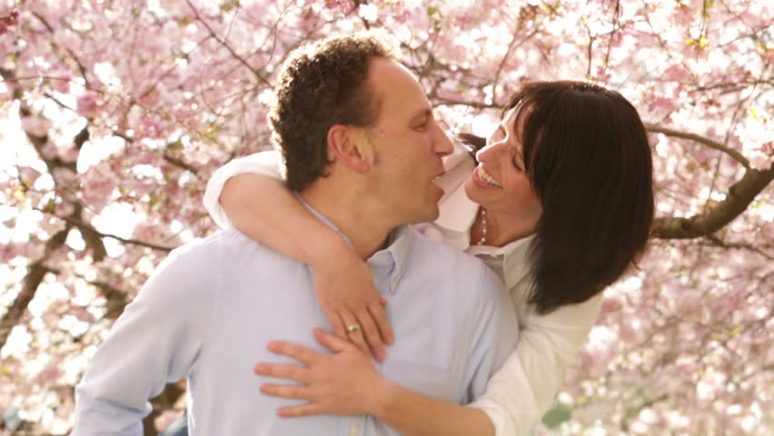 Mature man giving his wife a piggyback ride, both having fun and the loving couple kissing in the end with cherry trees in background