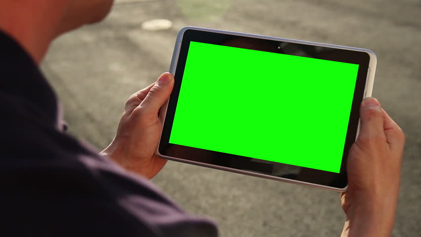 A man holds a blank tablet PC with a green screen for your own custom content. | Shutterstock Video #3833249