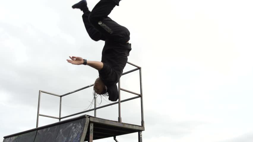 Parkour Jump - A free runner flips off a skateboard ramp in super slow motion