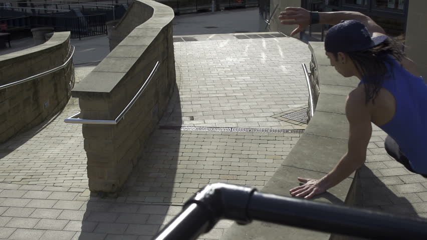 Parkour - tracking shot of a free runner vaults a wall in super slow motion