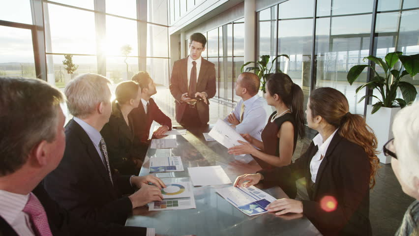 A confident and attractive business team of mixed ages and ethnicity are holding a meeting in a light, modern office building. They are discussing ideas for their business development.  | Shutterstock Video #3849596