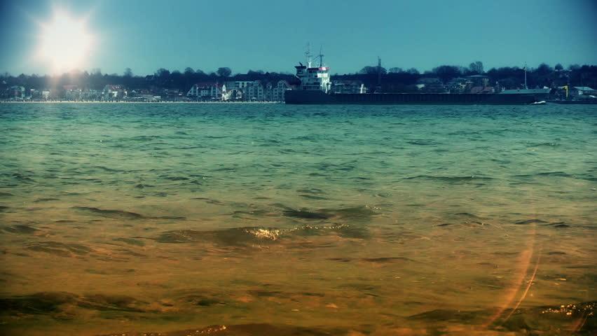 Cargo ship and speed boat passing near coastline