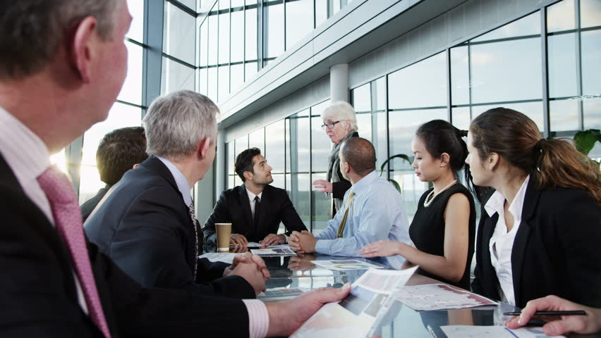 A confident and attractive business team of mixed ages and ethnicity are holding a meeting in a light, modern office building. They are discussing ideas for their business development.  | Shutterstock HD Video #3858029