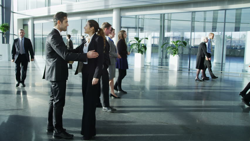 Attractive young businessman and businesswoman meet and shake hands in a busy modern office building. In the background other workers can be seen walking around the building .  | Shutterstock HD Video #3870632
