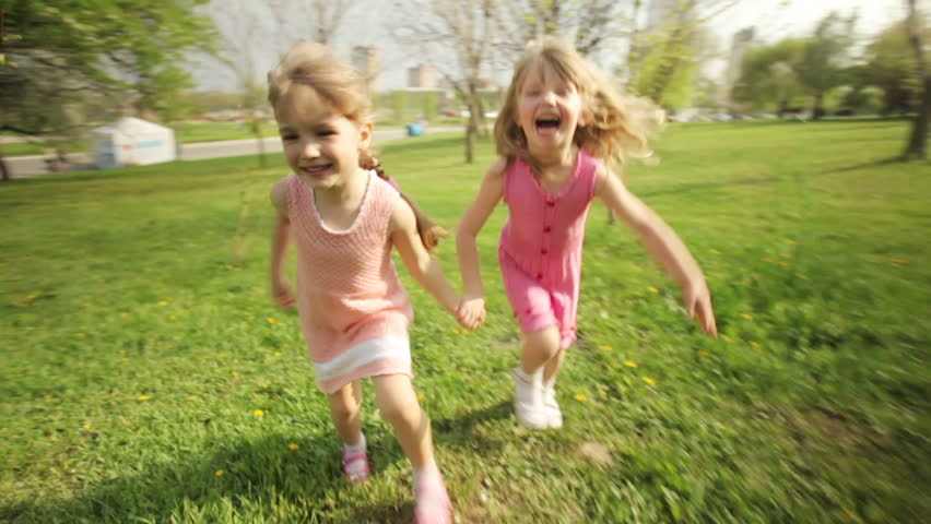 Sisters running around in garden and laughing