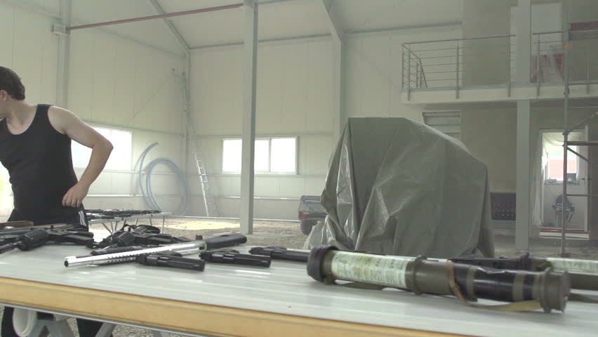 Russion wapon dealer firing rifle in warehouse