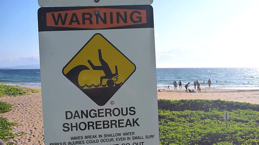 Dangerous shore break sign posted at beach in Hawaii on Maui.