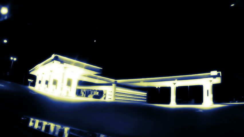 Dark night. The car drives through an empty gas station. Gas station illuminated