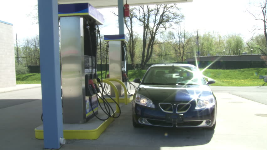 Wide view as car approaches the pumps at a gas station on a sunny day.  Camera