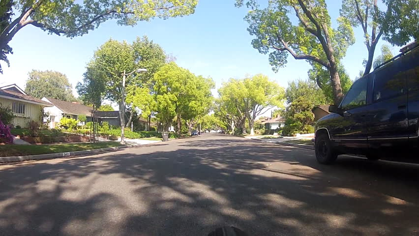 The point of view of someone riding a bicycle down the middle of a suburban