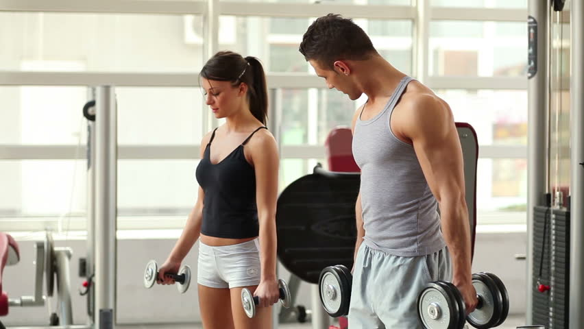 Young man and woman relaxing and exercising at the gym.
