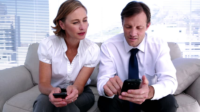 Businesswoman showing colleague how to work smartphone sitting on office couch | Shutterstock HD Video #4050625