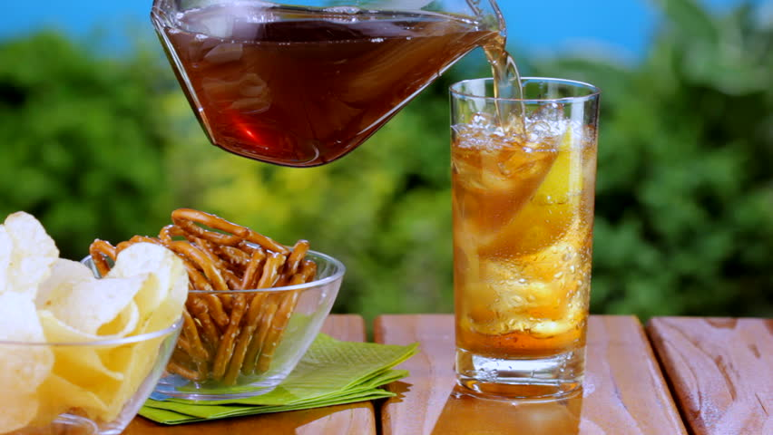 Pitcher pours iced tea into glass at outdoor picnic table