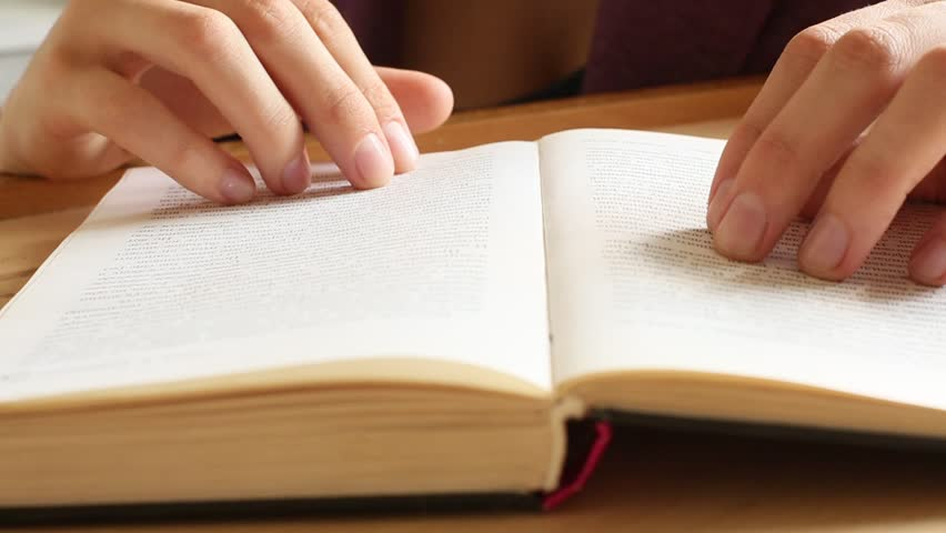 Women's hands leafing through a book (HD)