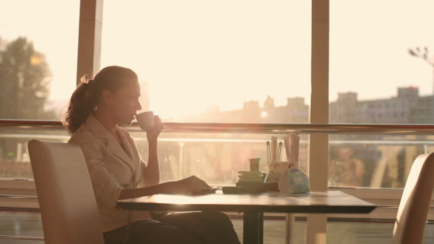 a young, beautiful woman drinking coffee | Shutterstock Video #4087387