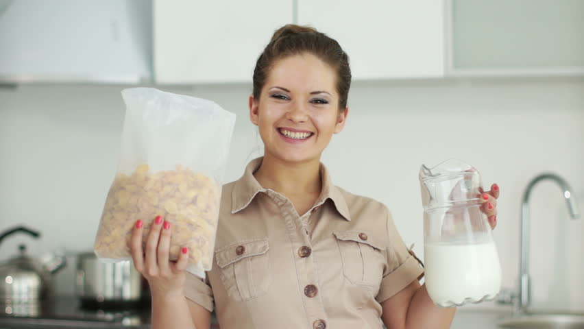 Woman standing in kitchen with cornflakes and milk