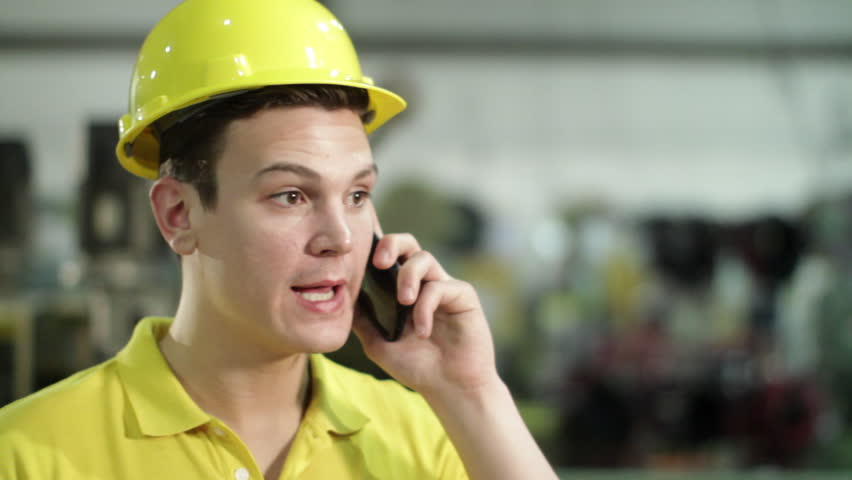 Contractor in hard hat on angry phone call in industrial setting.