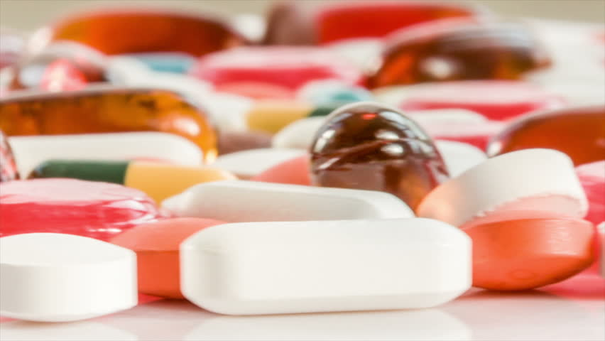 Medical pills placed on rotating table, shot with white seamless background
