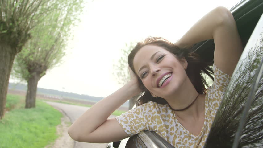 Young woman sitting in car passenger seat looking out window on sunny day with flare