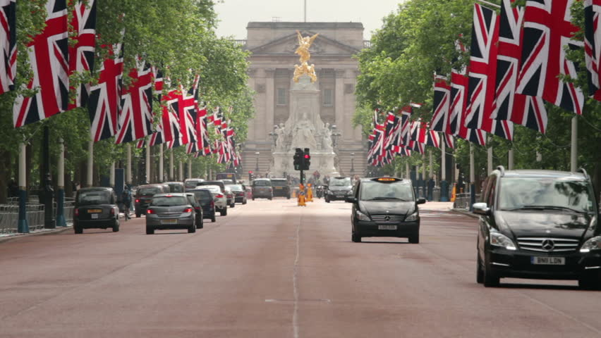 LONDON - JUNE 12:Traffic drives down The Mall towards Buckingham Palace with British flags along the road in preparation for the Trooping of the Colour on June 12, 2013 in London.
