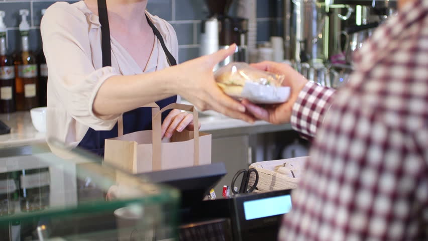 Female seller serving young man sandwich to go