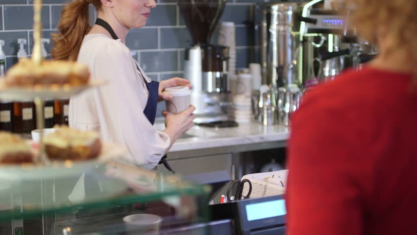 Female seller serving young woman coffee to go