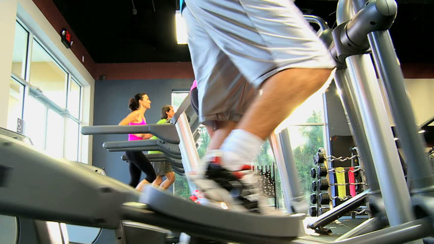 Gym members exercising on modern cross walker and treadmill equipment