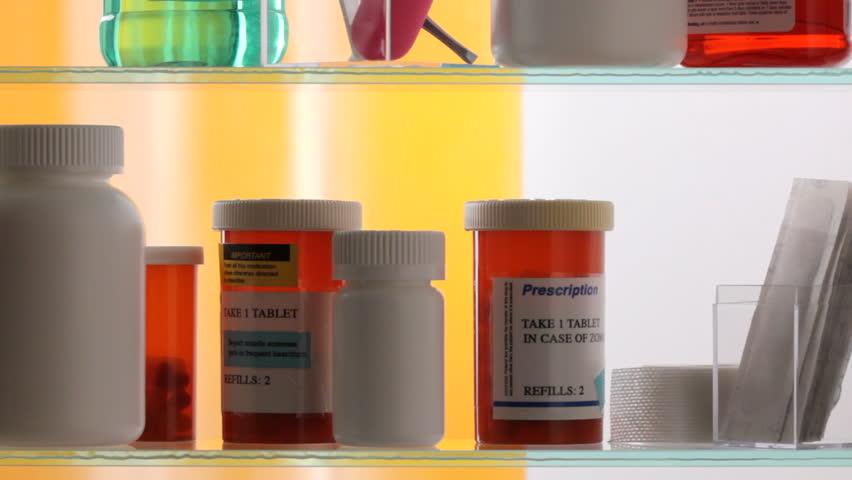 Medicine cabinet door opens, hand takes prescription drugs and closes door, shot