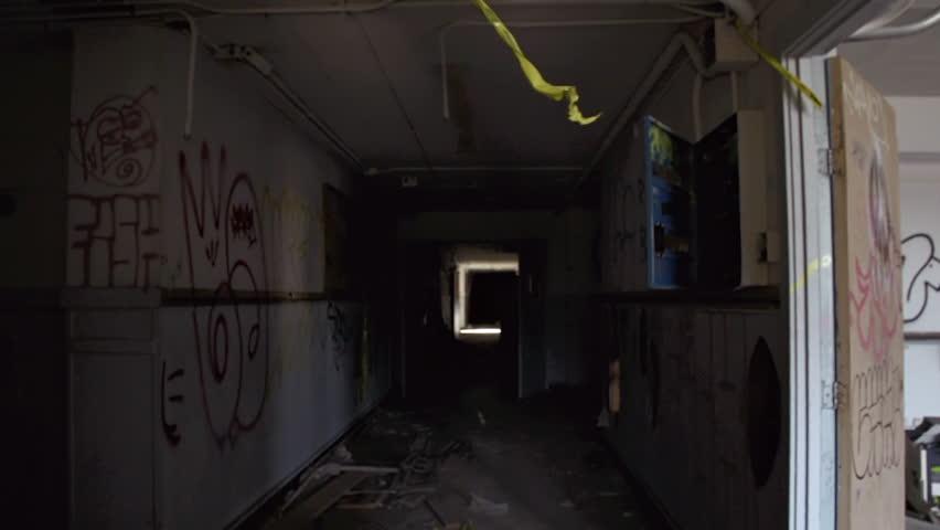 Handheld POV shot in hallway of a derelict abandoned urban building
