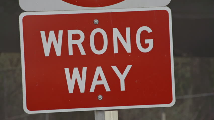 Rack focus to red Wrong Way sign on an exit ramp