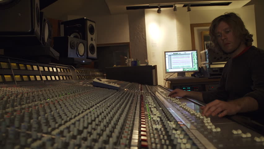 A young studio engineer working at a large SSL mixing board in recording studio.