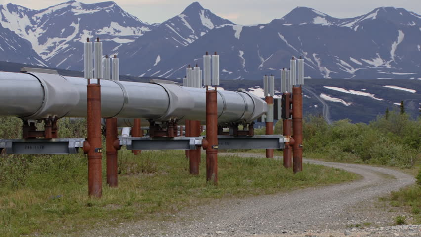 Trans-Alaskan Pipeline snaking up a far-off hill toward distant mountains
