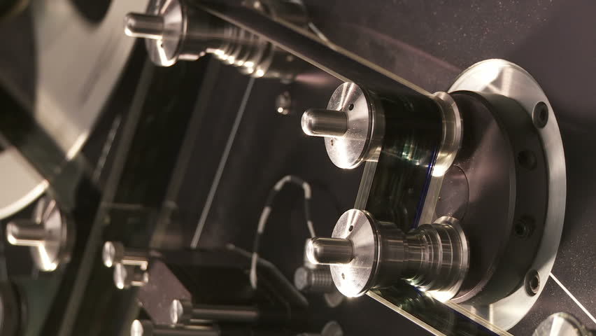 Detail of 35mm film moving around tension rollers in a telecine machine in a