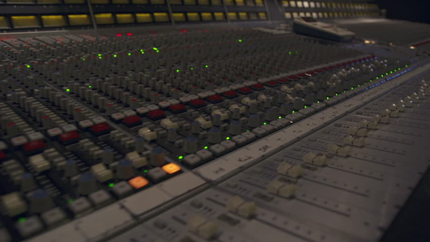 Swooping across the faders and channels of an SSL recording board in a music