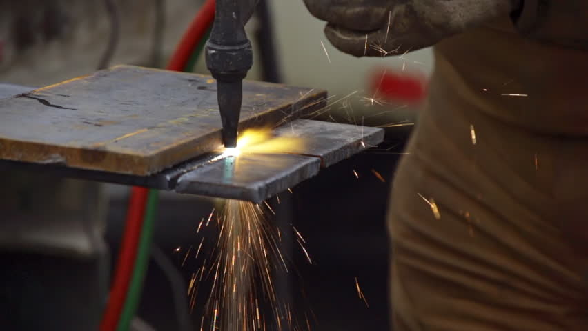 Close-up of an industrial worker cutting a steel plate with an oxy-acetylene