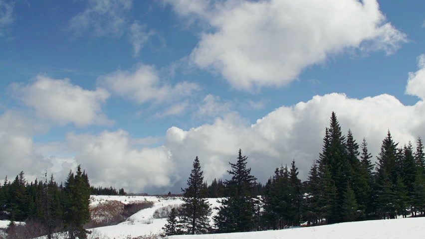 Time lapse of storm clouds gathering to blot out a bright blue sky over a snowy