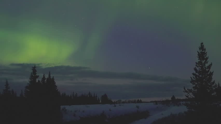 Aurora borealis time lapse lights over snowy landscape and forest in Alaska