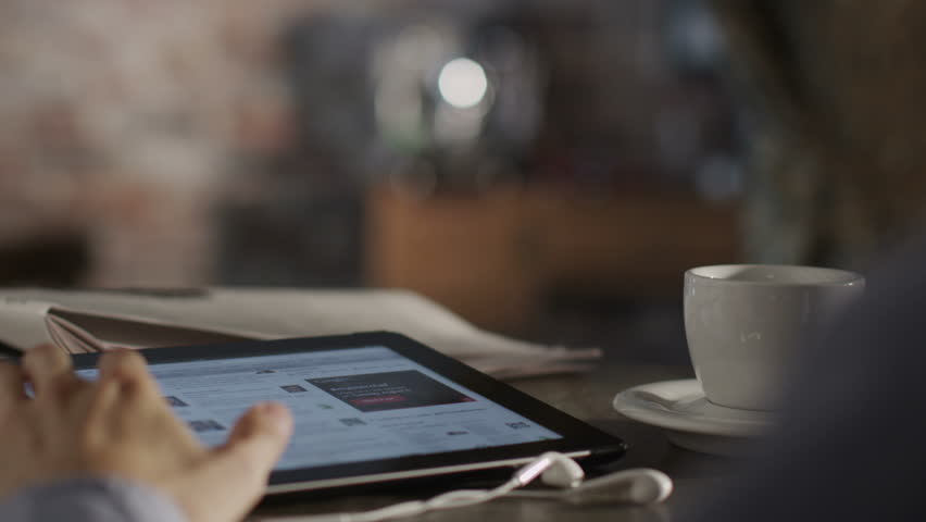 Man Reading News with Digital Tablet and Drink Coffee. Shot on RED Digital Cinema Camera in 4K (ultra-high definition (UHD)), so you can easily crop, rotate and zoom, without losing quality!