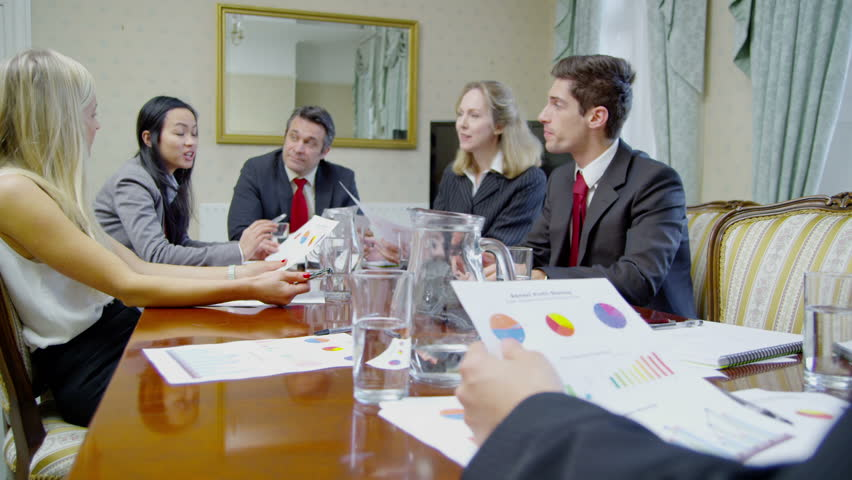 Successful professional team of mixed ages and ethnicity are seated around a conference table for a business meeting. They are looking at printed diagrams and discussing their business strategy.  | Shutterstock HD Video #4375565