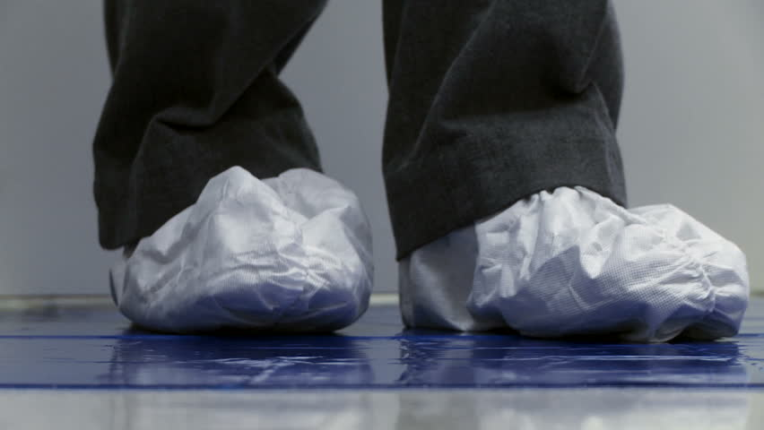 Close up of feet wearing paper boots coming out of a clean lab environment.