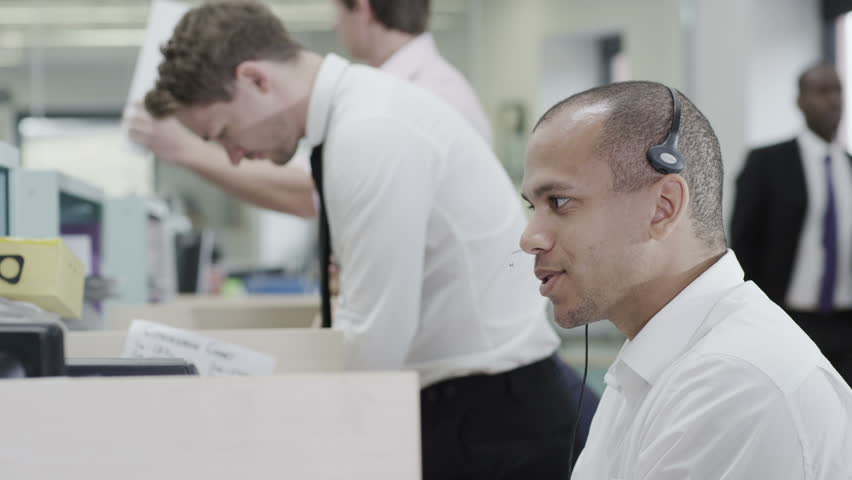Cheerful young customer service operator, at work in a busy call center | Shutterstock HD Video #4390580