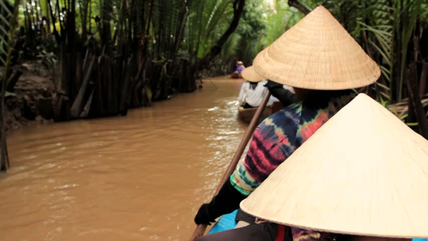 MEKONG DELTA, VIETNAM - JULY 24: woman rows a boat on a canal, Vietnam on July