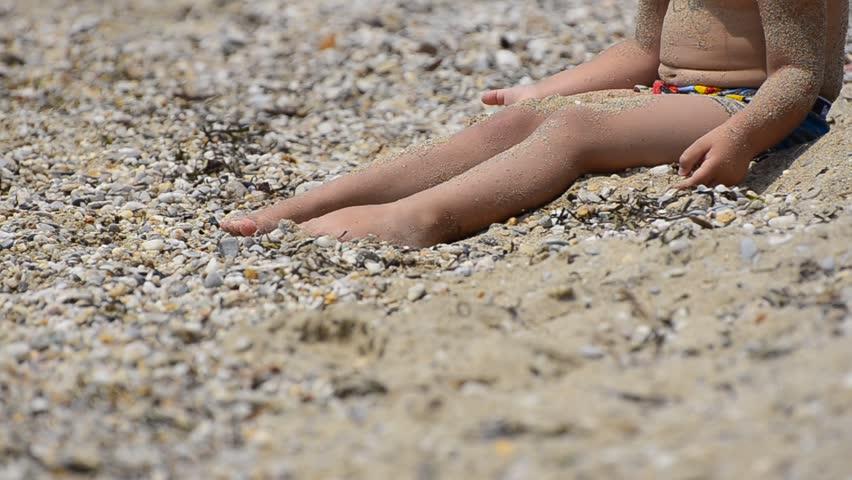 Summer beach, little child plays with send stones on an empty ocean beach