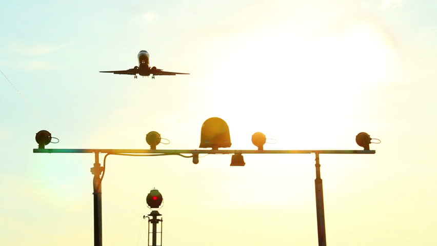 Landing light post as aircraft landing at dusk, through sun rays