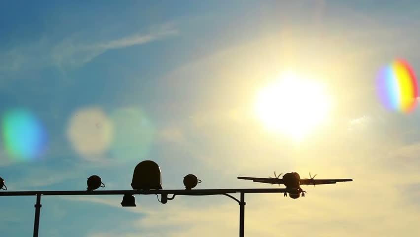 Airliner lands flying above camera, landing light posts, daytime
