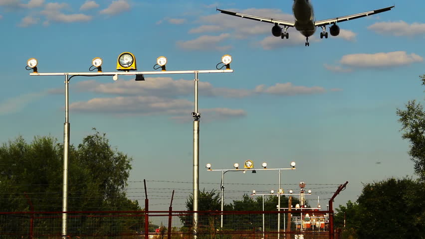 Landing aircraft with shadow above earth, landing light posts