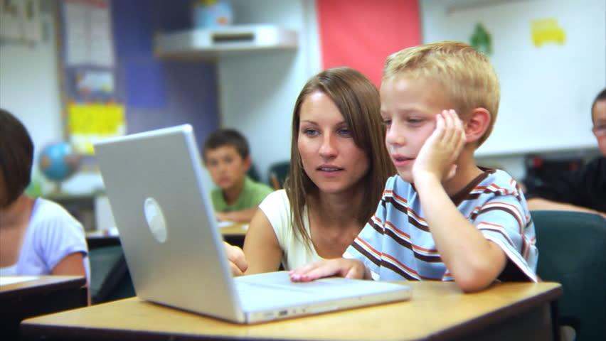 Elementary school student and teacher look at computer   Shutterstock HD Video #4541270