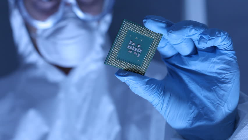 Man in clean room holds up computer cpu microchip